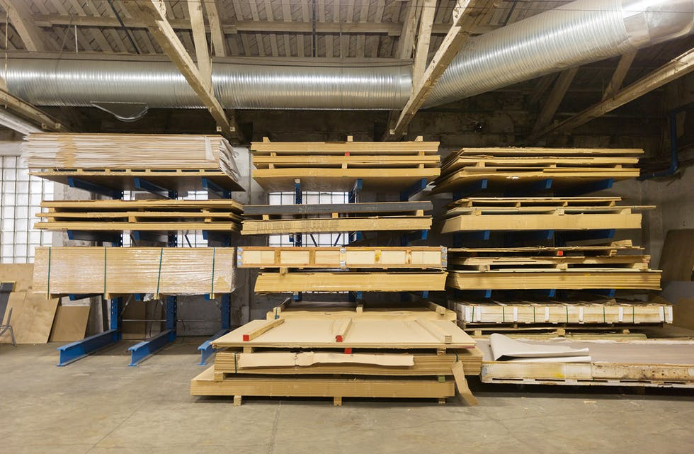 production, manufacture and woodworking industry concept - boards storing at factory warehouse